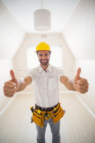 Handyman smiling at camera in tool belt Stock photo © wavebreak_media