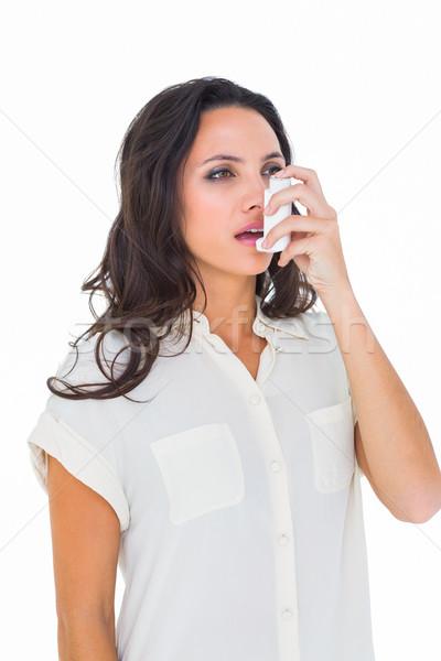 Asthmatic brunette using her inhaler  Stock photo © wavebreak_media