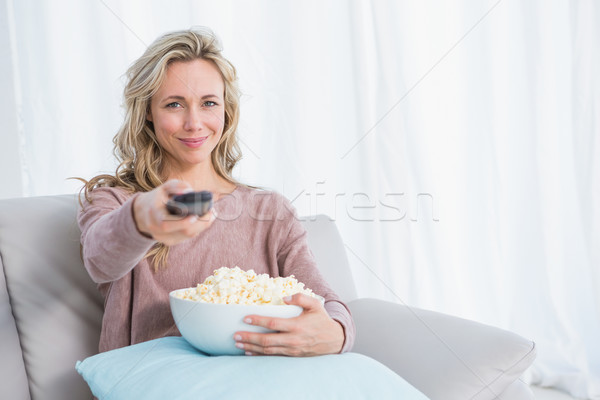 Smiling blonde changing tv channel while eating popcorn Stock photo © wavebreak_media