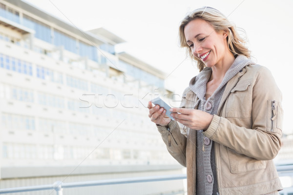 Smiling blonde standing and text messaging Stock photo © wavebreak_media