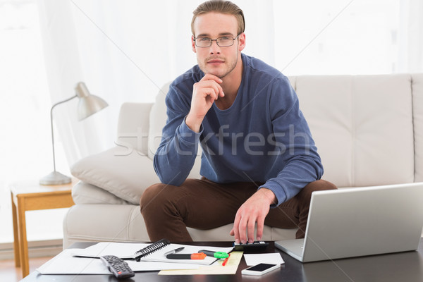 Thoughtful man hand on chin using calculator Stock photo © wavebreak_media