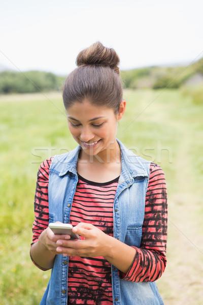 Pretty brunette texting in the park Stock photo © wavebreak_media