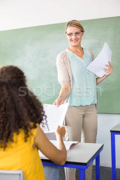 Female teacher handing paper to student Stock photo © wavebreak_media