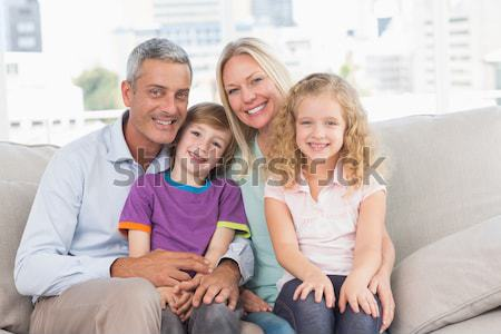 Happy family sitting with pet kitten together Stock photo © wavebreak_media