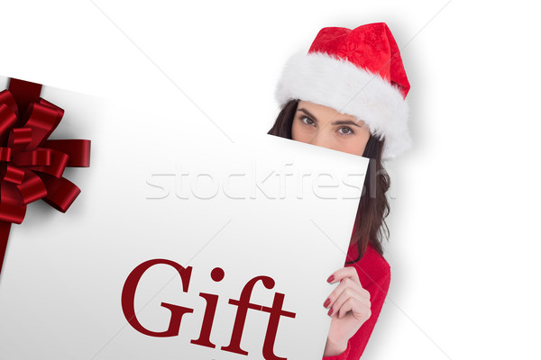 Composite image of beauty brunette in santa hat showing gift car Stock photo © wavebreak_media