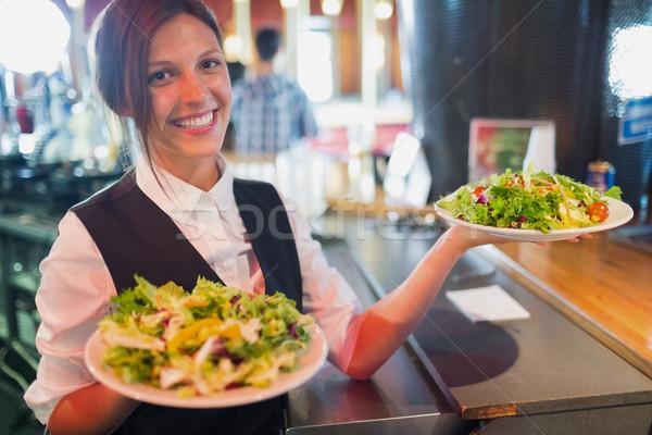 Pretty barmaid holding plates of salads Stock photo © wavebreak_media