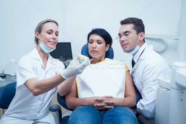 Dentists showing woman prosthesis teeth Stock photo © wavebreak_media
