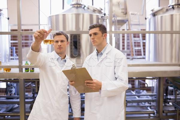Focused scientist team looking at beaker Stock photo © wavebreak_media