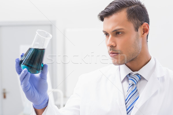 Concentrated scientist looking at beaker  Stock photo © wavebreak_media