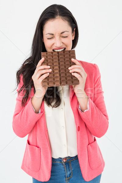 Brunette biting bar of chocolate Stock photo © wavebreak_media