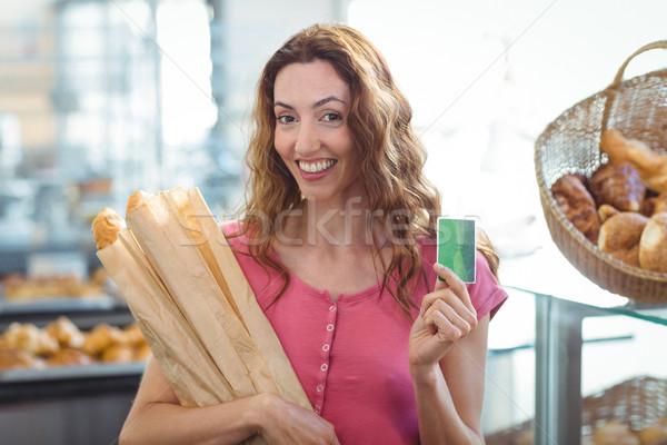 Joli brunette carte de crédit baguettes boulangerie Photo stock © wavebreak_media