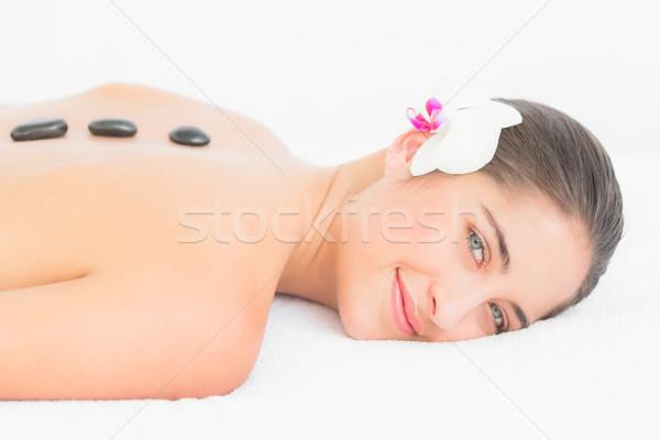 Pretty woman enjoying a hot stone massage Stock photo © wavebreak_media