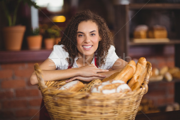Smiling waitress bended over a basket of bread Stock photo © wavebreak_media