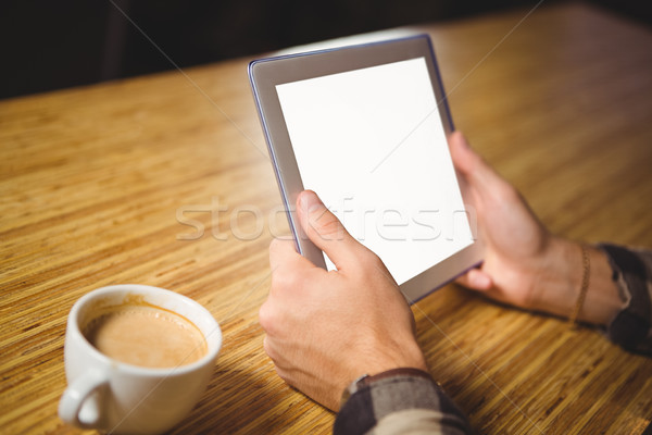 Man drinking coffee and using tablet computer Stock photo © wavebreak_media