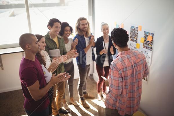 Team applauding while businessman discussing strategies Stock photo © wavebreak_media