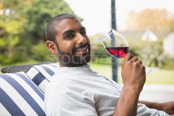 Mosolyog férfi iszik vörösbor megnyugtató veranda Stock fotó © wavebreak_media