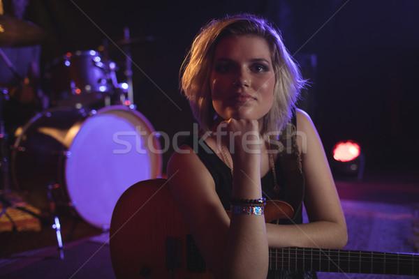 Confident female guitarist sitting in nightclub Stock photo © wavebreak_media