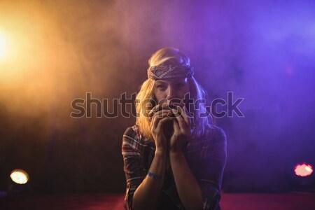 Vrouwelijke muzikant spelen mondharmonica verlicht discotheek Stockfoto © wavebreak_media