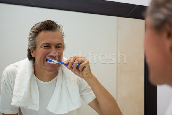 Man brushing his teeth in bathroom Stock photo © wavebreak_media
