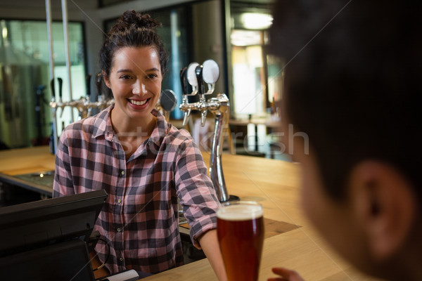 Smiling barmaid serving drink to man Stock photo © wavebreak_media