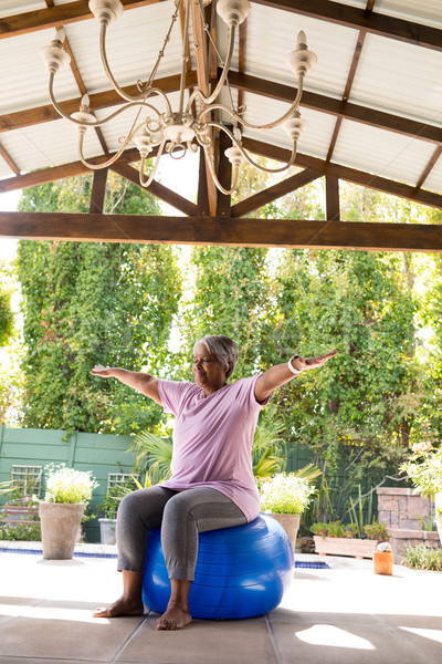 Full length of senior woman with arms outstretched sitting on exercise ball Stock photo © wavebreak_media