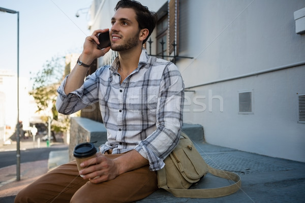 Man talking on mobile phone while sitting on retaining wall Stock photo © wavebreak_media