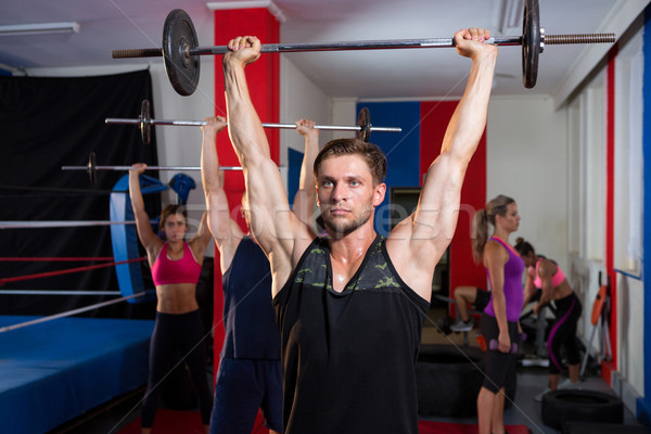 Young athletes lifting barbells with arms raised Stock photo © wavebreak_media