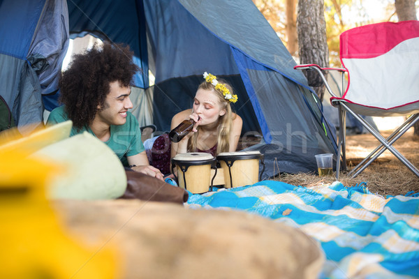 Woman having drink while relaxing with boyfriend in tent Stock photo © wavebreak_media