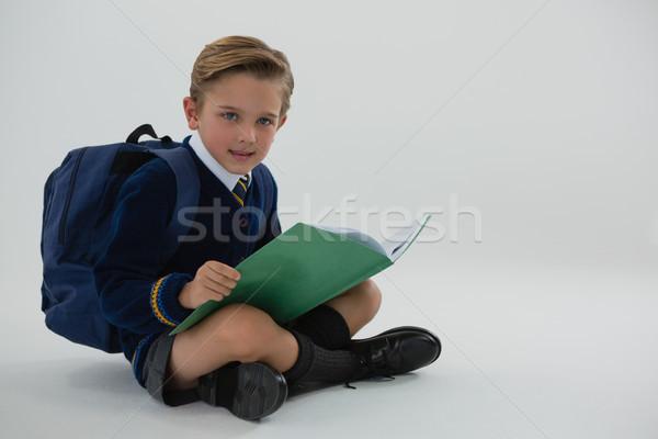 Schoolboy reading book while sitting on white background Stock photo © wavebreak_media