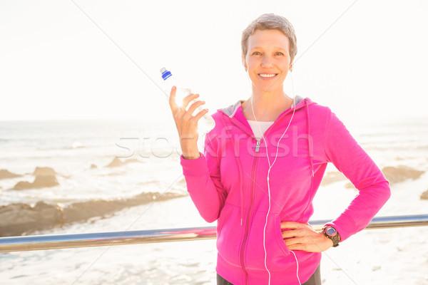 Smiling sporty woman with headphones holding bottle Stock photo © wavebreak_media