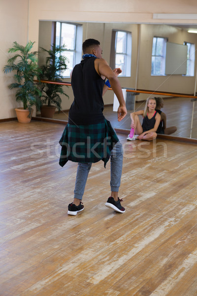 Male dancer rehearsing with friend sitting at studio Stock photo © wavebreak_media