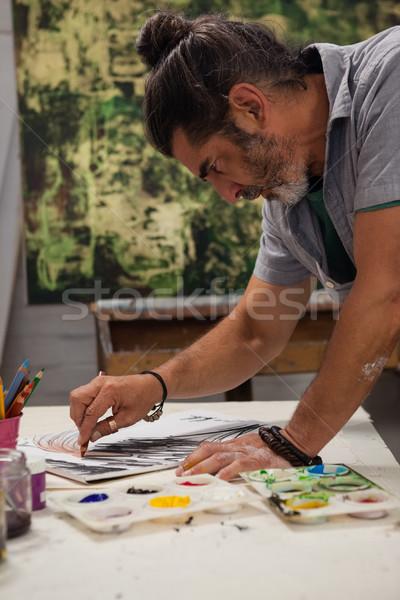 Attentive man painting at table Stock photo © wavebreak_media