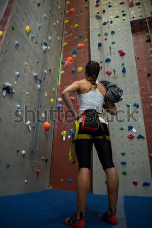 Athlete with rope looking up while standing by climbing wall in club Stock photo © wavebreak_media
