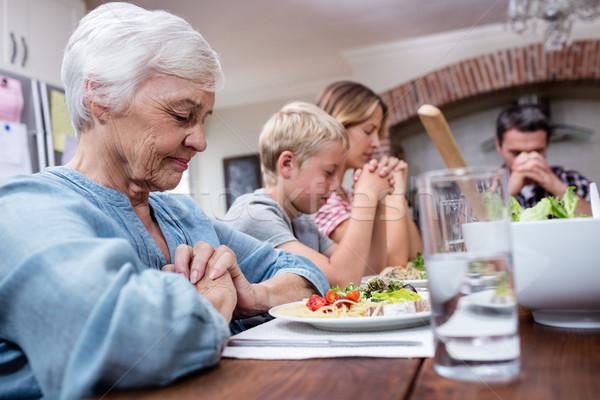 Multi-generation family praying before having meal Stock photo © wavebreak_media