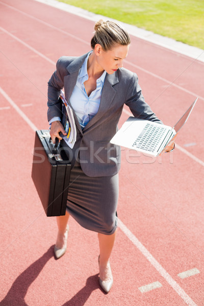 Businesswoman ready to run with a laptop and briefcase Stock photo © wavebreak_media
