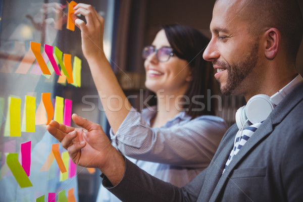 Munkatársak tapadó jegyzetek üveg kreatív iroda Stock fotó © wavebreak_media