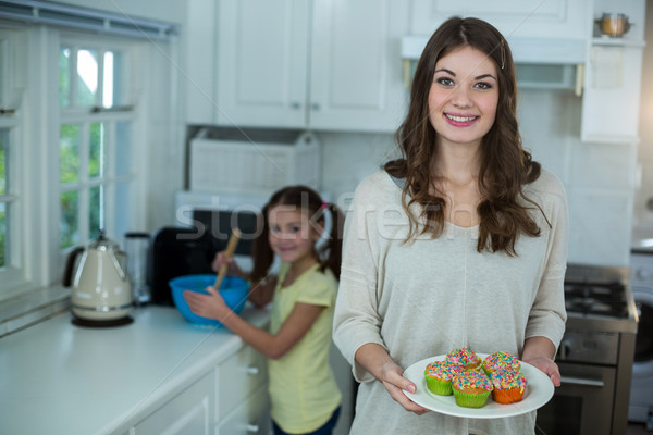 Woman holding a plate of cupcakes while her daughter preparing breakfast Stock photo © wavebreak_media