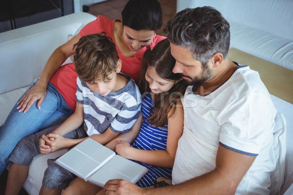 Famiglia seduta divano guardando photo album home Foto d'archivio © wavebreak_media