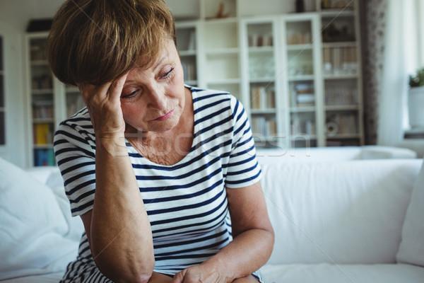Tense woman sitting on sofa in living room Stock photo © wavebreak_media