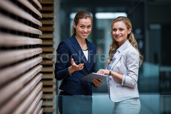 Business colleagues using digital tablet in office lobby Stock photo © wavebreak_media