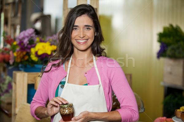 Smiling shop assistant holding a jar of pickle Stock photo © wavebreak_media