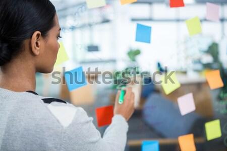 Hombre lectura notas adhesivas vidrio pared Foto stock © wavebreak_media
