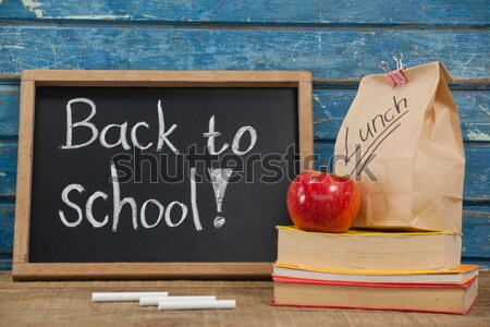 Slate with chalks by lunch bag and books on wooden table against green Stock photo © wavebreak_media