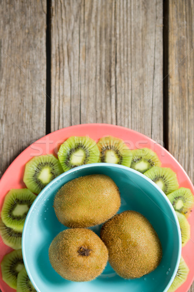 Kiwis arranged in bowl and plate on wooden table Stock photo © wavebreak_media