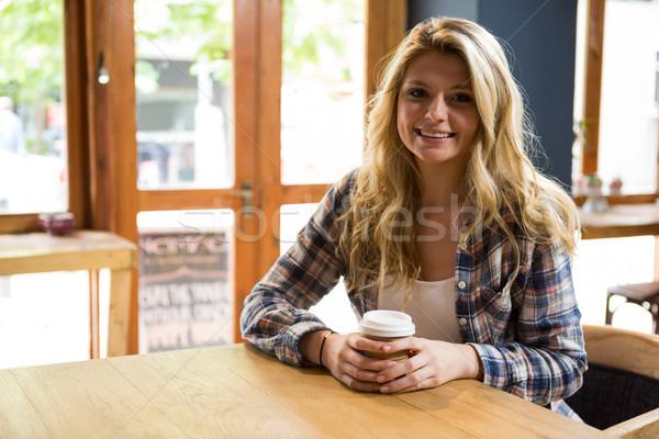 Mosolyog fiatal nő tart eldobható kávéscsésze kávézó Stock fotó © wavebreak_media