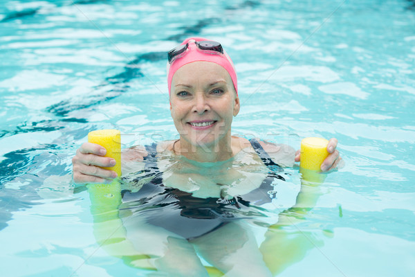 Mature woman swimming with pool noodle Stock photo © wavebreak_media