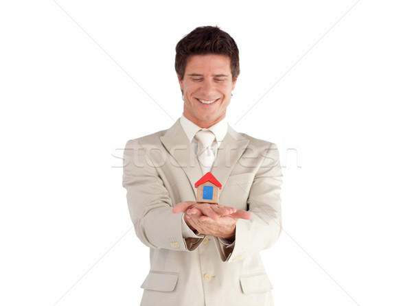 Attractive young businessman presenting a sample of house against a white background Stock photo © wavebreak_media