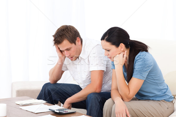 Worried couple looking at their bills on the sofa at home Stock photo © wavebreak_media