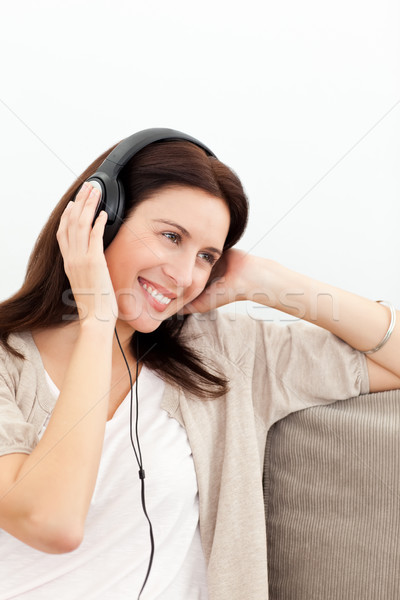 Woman smiling while listening music on the sofa Stock photo © wavebreak_media