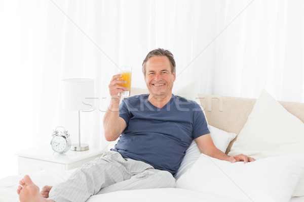 Retired man looking at the camera while he is drinking oranje juice at home Stock photo © wavebreak_media